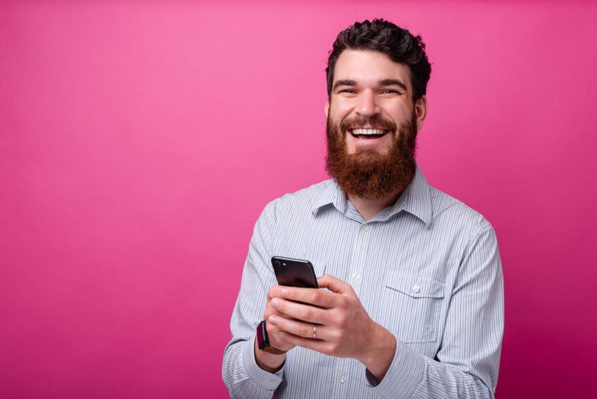 Lachender Mann mit Smartphone nutzt eine Dating App