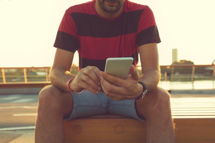 Ein Mann benutzt eine Dating-App auf seinem Handy auf der Suche nach einem Partner