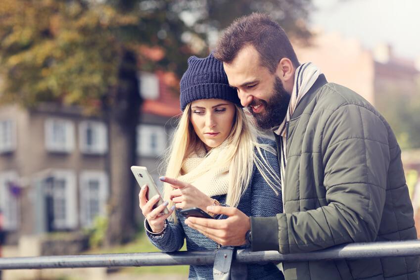 Paar, das über ein Handy auf einer Brücke interagiert.