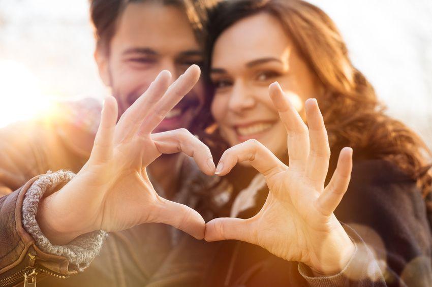 Verliebtes christliches Paar, das mit den Händen einen Herd baut