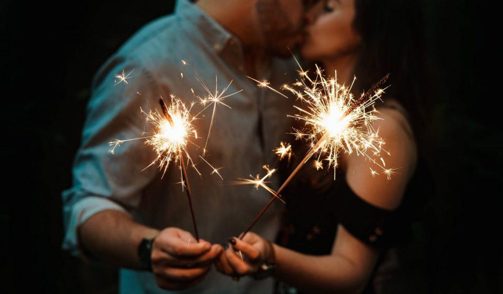 Pärchen mit brennenden Wunderkerzen küsst sich