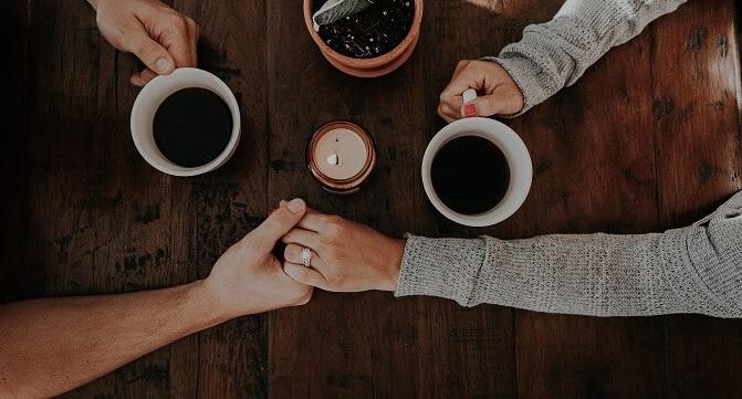 Paar, das beim gemeinsamen Kaffeetrinken Händchen hält