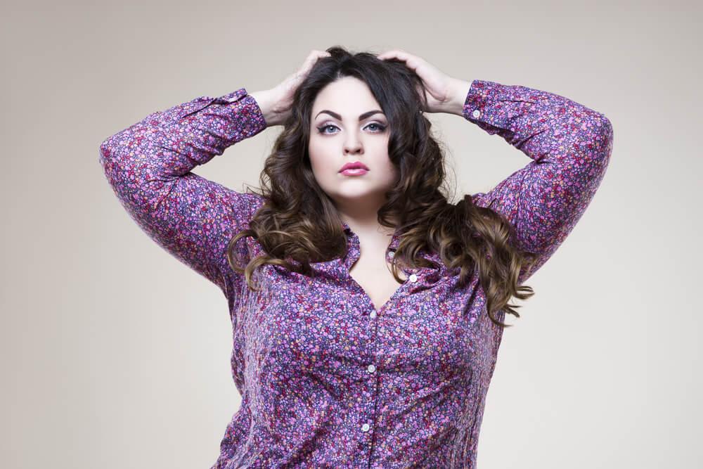 Charmante kurvenreiche Frau mit lila Hemd, die ihre Arme auf den Kopf legt
