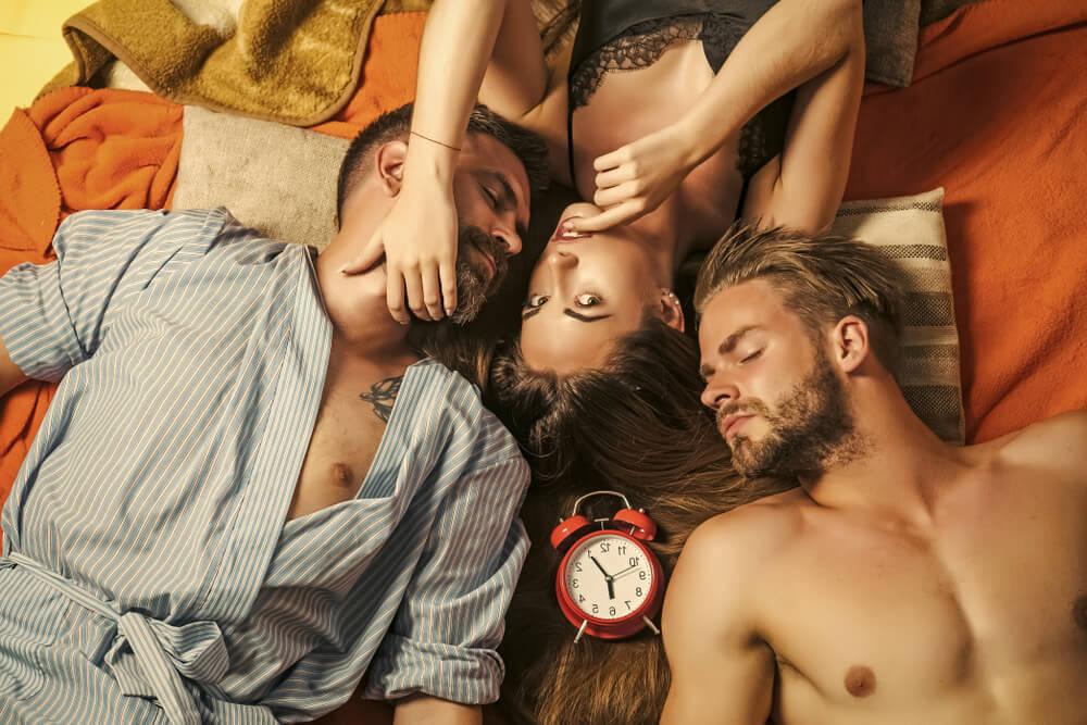 Zwei sexy Männer und eine heiße Frau liegen zusammen im Bett, bereit für eine Swinger-Nacht