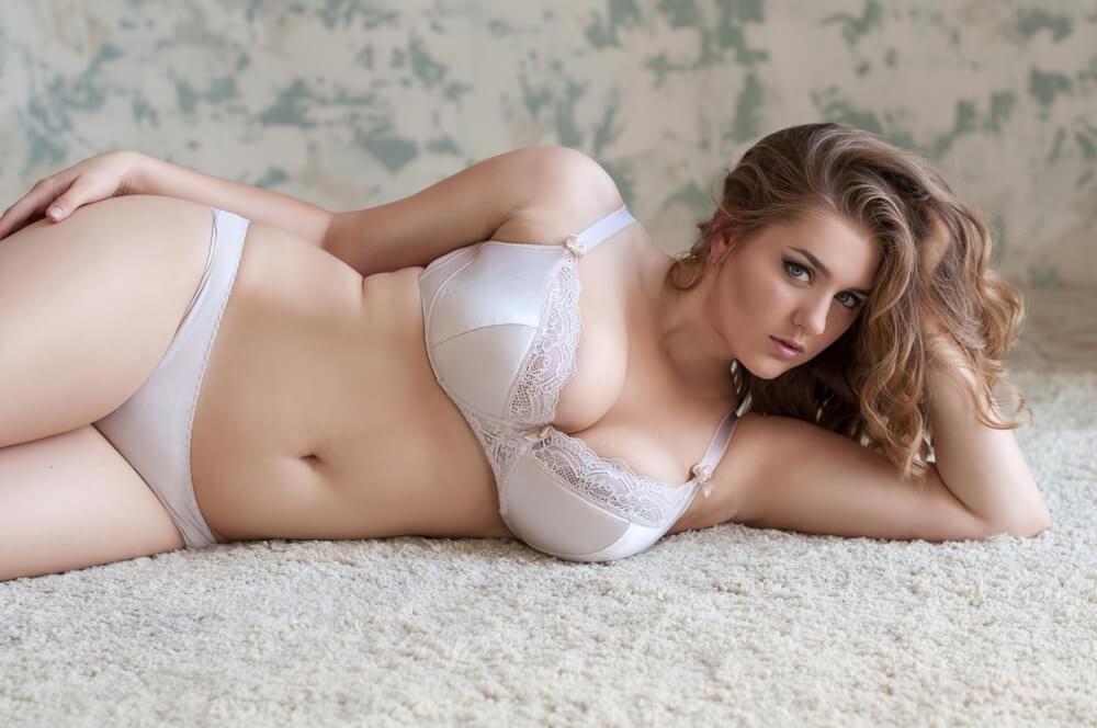 Sexy kurvenreiche Frau, die mit BH und Unterwäsche auf dem Teppich liegt und in die Kamera starrt.