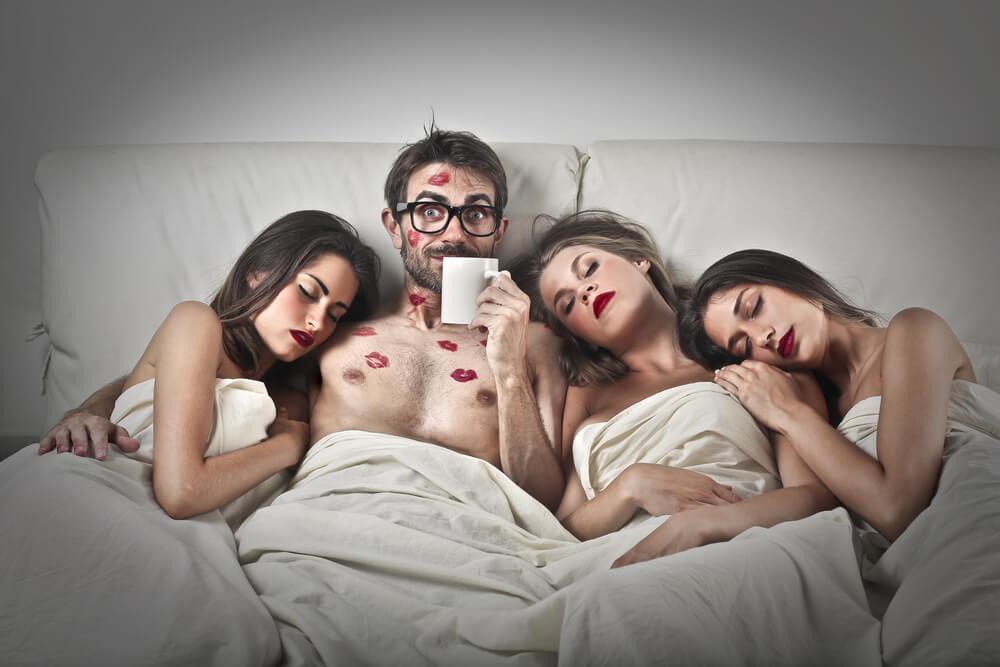 Ein Typ mit drei schönen Frauen, die im Bett liegen. Der Mann hat Kussmarken auf Gesicht und Brust.