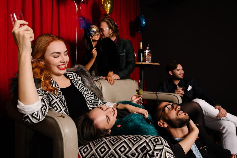 Stilvolle Männer und Frauen feiern eine Swinger-Party, sie alle lächeln und haben Spaß.