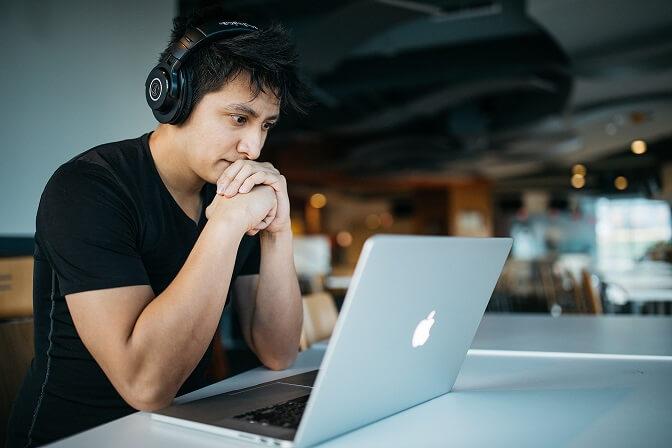 Asiatischer Single aktiv auf seinem Laptop mit Kopfhörern