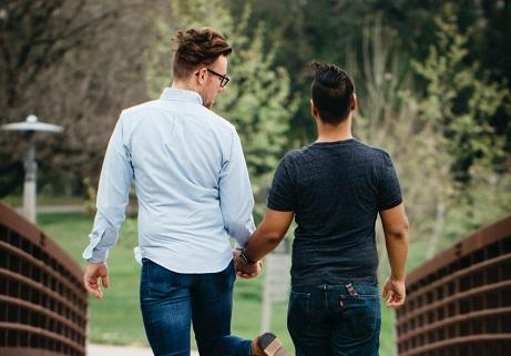 ein schwules Paar, das Händchen hält und spazieren geht