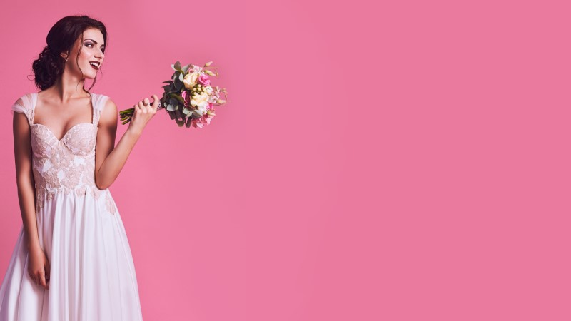 bestellte Braut im Hochzeitskleid zeigt ihren Blumenstrauß