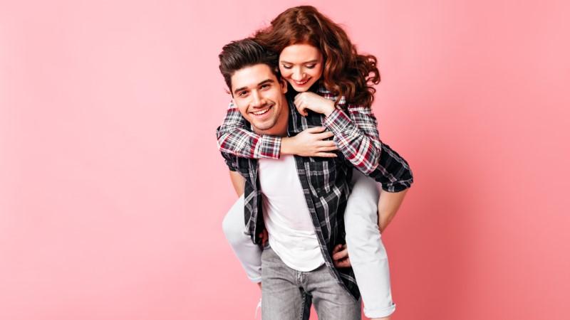 Asexueller brünetter Mann trägt seine rothaarige Freundin Huckepack