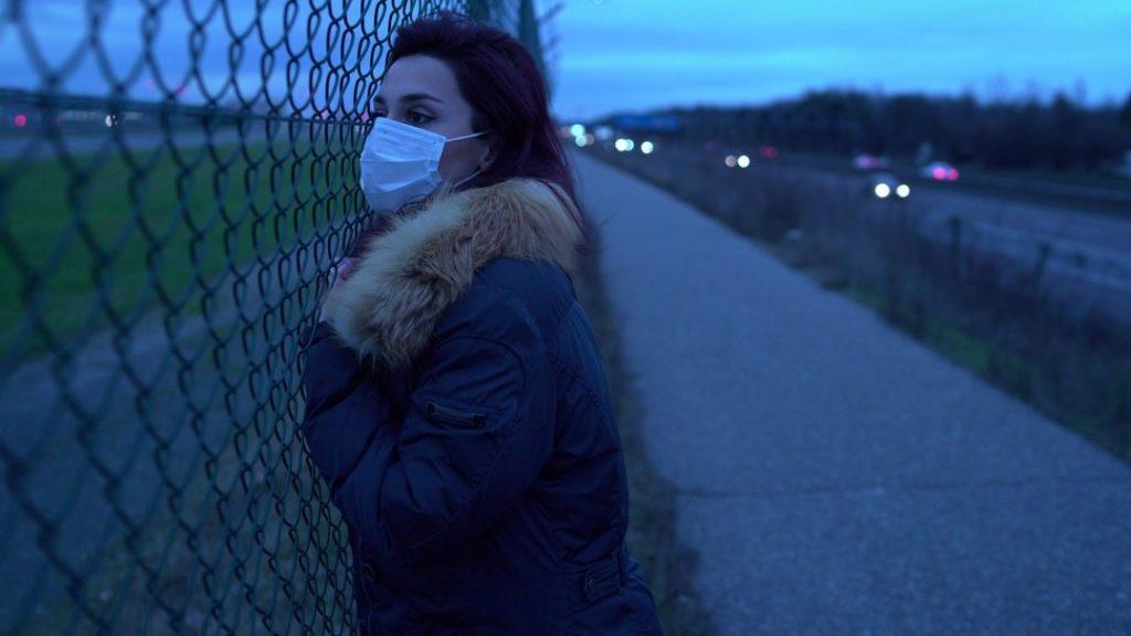 Frau mit Maske schaut sehnsüchtig in die Ferne am Zaun
