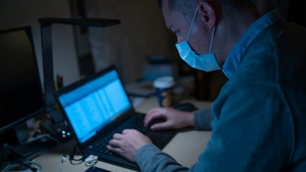 Mann in Maske am Laptop