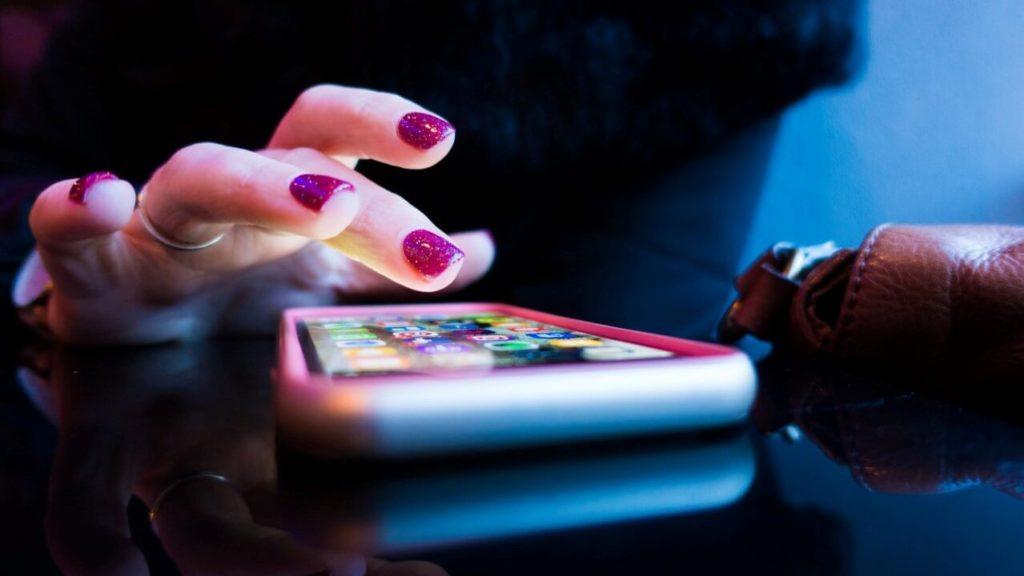 Frauenhand über einem Smartphone