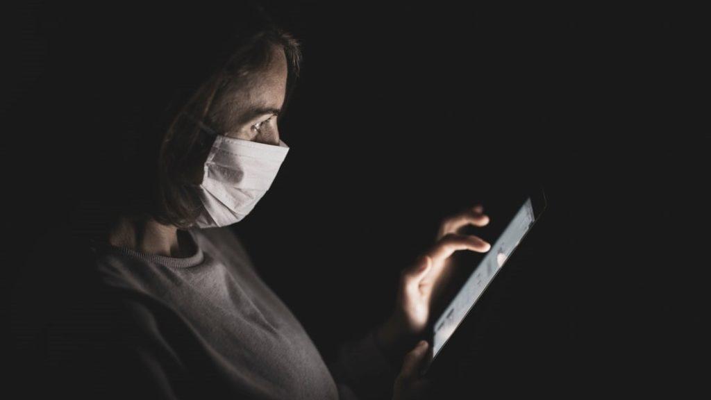 Eine Frau in einer Maske im dunklen, die auf ein Tablet schaut
