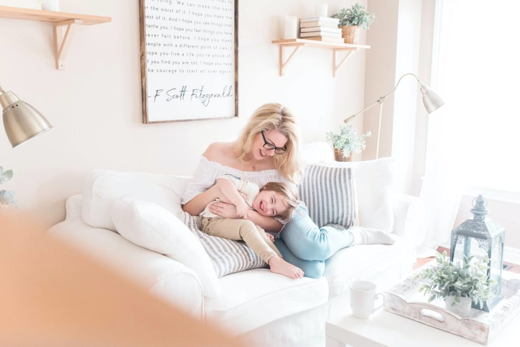 Alleinerziehende Mutter kuschelt mit ihrem Kind auf der Couch