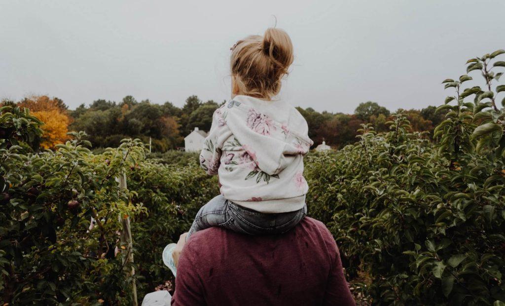 Single-Vater trägt seine Tochter auf den Schulter umgeben von Bäumen