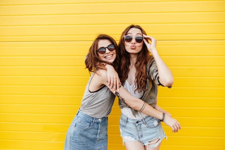 Zwei flirtende Frauen mit Sonnenbrillen