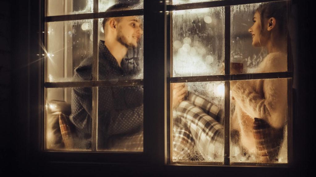Holidating Pärchen hinter einem Fenster
