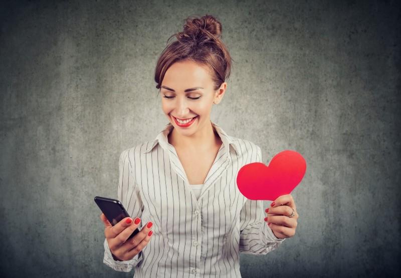 Glückliche und hübsche Frau mit einem Papierherzen in der einen und einem Smartphone in der anderen
