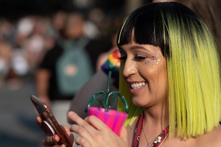 Frau mit gelben Haaren flirtet am Handy