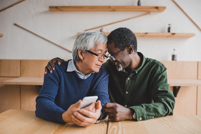 Ein älterer schwuler asiatischer Mann und ein älterer schwuler schwarzer Mann sitzen glücklich zusammen an einem Tisch und berühren sich an den Stirnen.