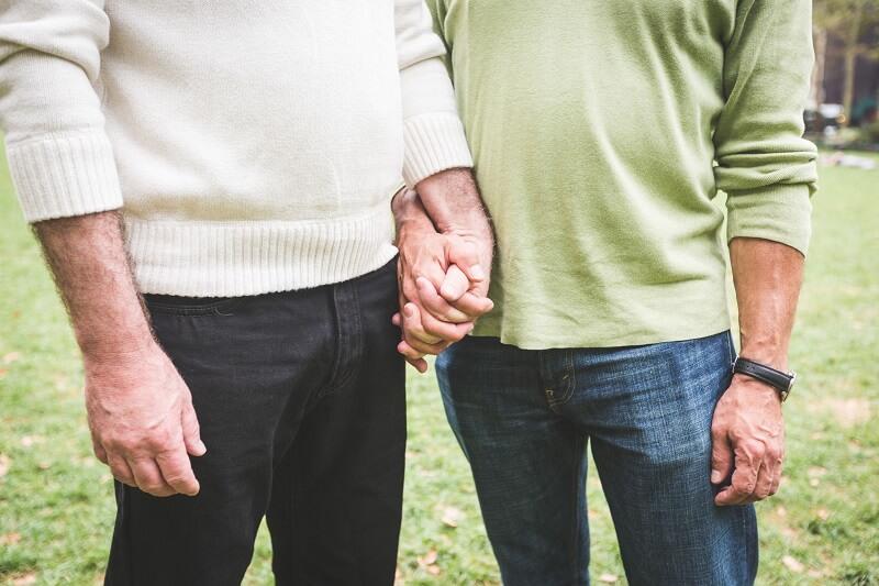Zwei schwule ältere Männer halten sich in einem Park an den Händen.