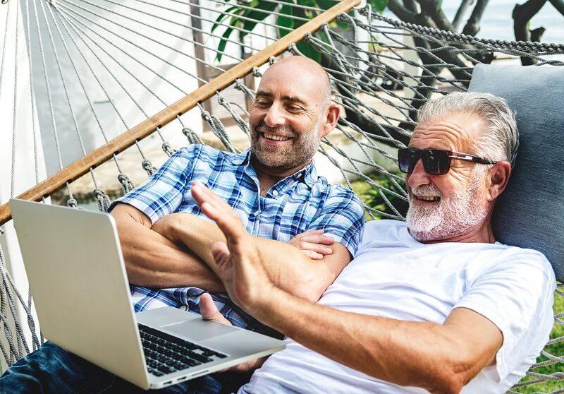 Zwei ältere schwule Männer, die fröhlich zusammen einen Laptop benutzen.