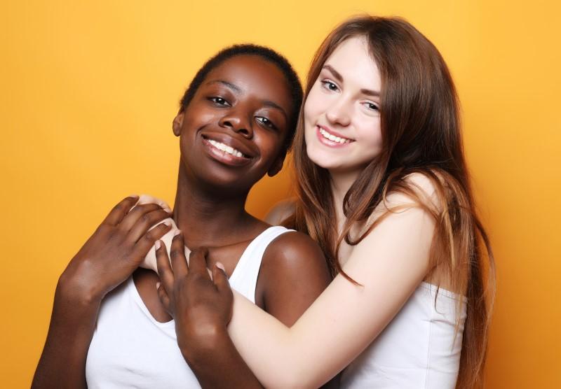 lesbisches Pärchen umarmt sich lächelnd