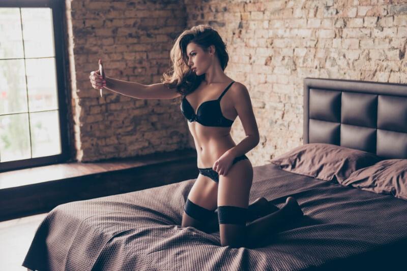 Frau in Dessous posiert für ein Foto für ihr Dating-Profil