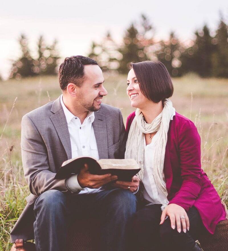 Verliebtes Paar, das gemeinsam eine Bibel liest