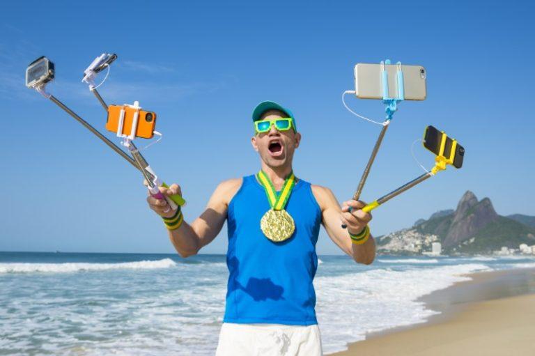 verrückter Kerl nimmt lustiges Selfie mit mehreren Selfie-Sticks am Strand auf
