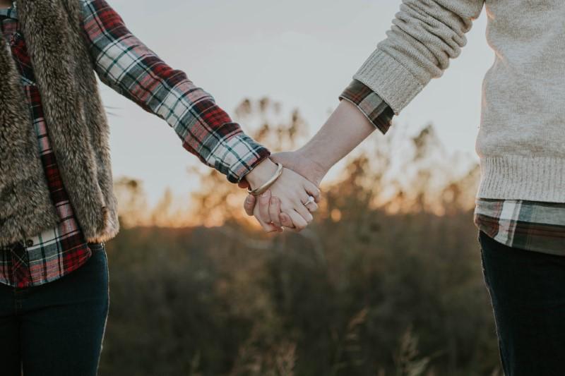 zwei Menschen halten sich draußen an den Händen