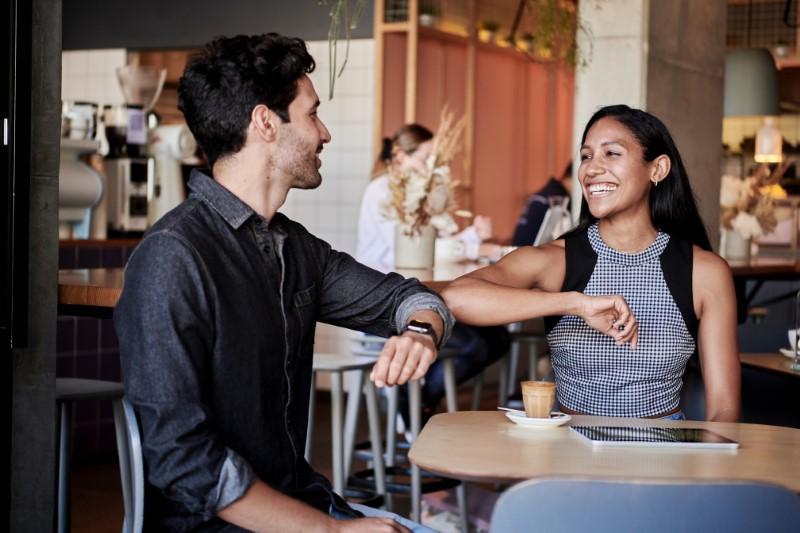 zwei Personen bei einem Date berühren sich mit den Ellenbogen