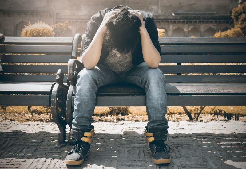 Mann sitzt auf einer Bank und hält seinen Kopf