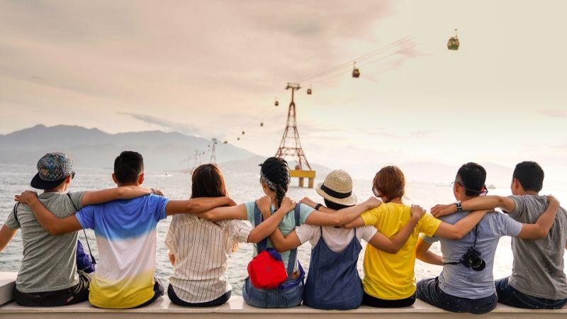 Freunde, die zusammensitzen, sich umarmen und die Landschaft beobachten