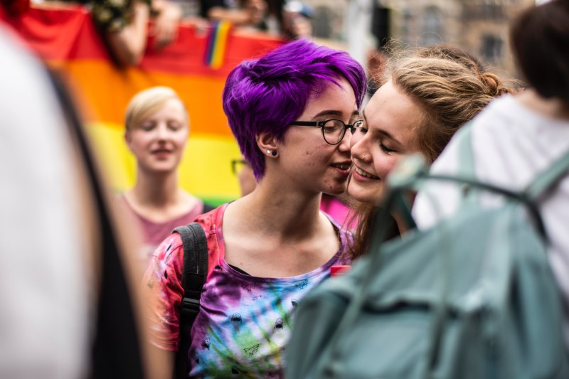 zwei junge Mädchen küssen sich bei einem Pride-Marsch.