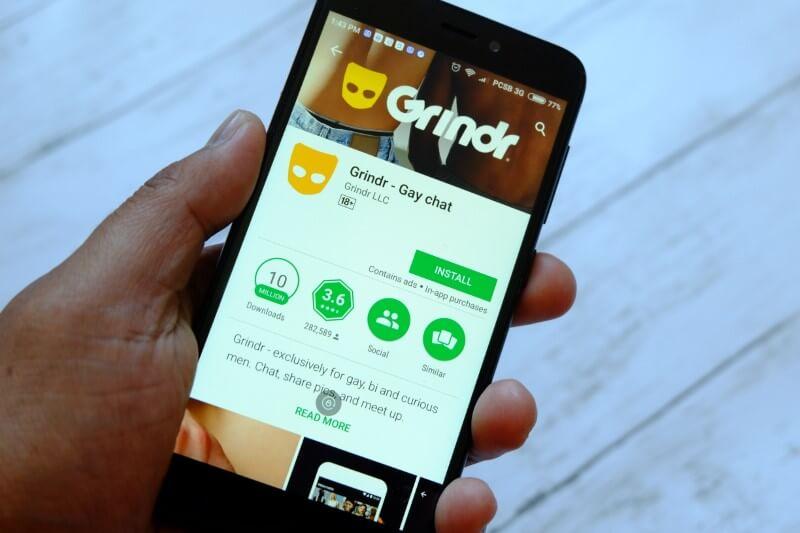 jemand mit einem Smartphone mit Grindr im App Store