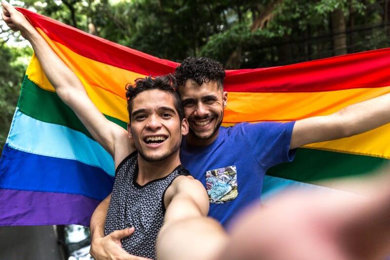 Selfie von zwei Männern mit einer Gay-Pride-Flagge